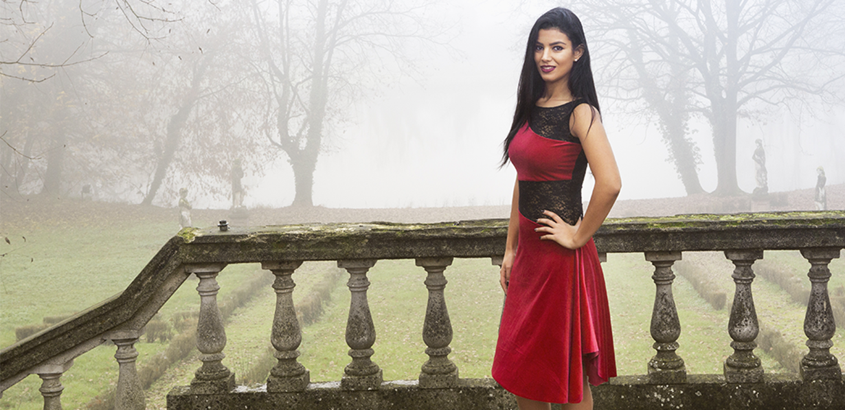 A woman wearing a red and black Tango dress in a misty background