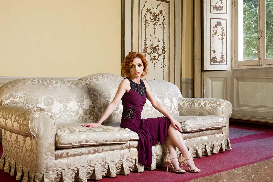 A woman in a maroon Tango dress sitting on sofa