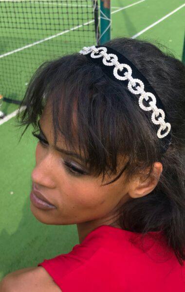 A flat black velvet headband with rhinestones